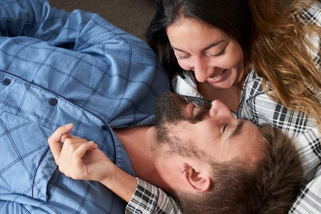 Gros plan jeune couple habillé en pyjama à la maison. ils se regardent amoureux avec un sourire sincère.