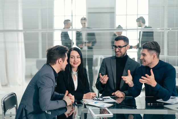 Gros plan .jeune employé expliquant ses idées à ses collègues.