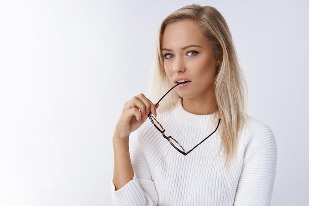 Gros plan d'une jeune employée blonde sensuelle attrayante et réfléchie dans des lunettes élégantes à cadre en chandail et en regardant la caméra en profondeur, pensant posant sérieusement sur fond blanc.