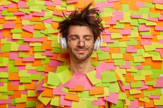 Gros plan sur un jeune étudiant entouré de notes autocollantes