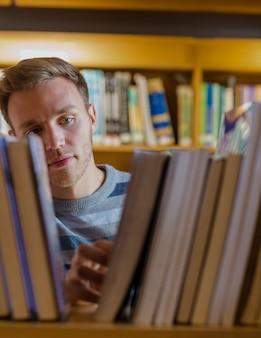 Gros plan d'un jeune étudiant sélectionnant un livre dans la bibliothèque de la bibliothèque de l'université