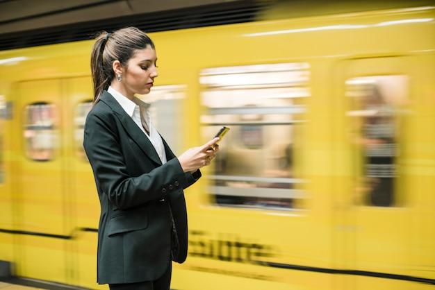 Gros plan d'une jeune femme d'affaires à l'aide de téléphone portable à la station de métro