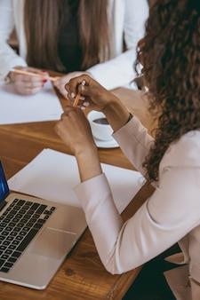 Gros plan sur une jeune femme d'affaires dans un bureau moderne avec une équipe. réunion créative, attribution de tâches. les femmes travaillant au front-office. concept de finance, d'affaires, de pouvoir des filles, d'inclusion, de diversité, de féminisme.