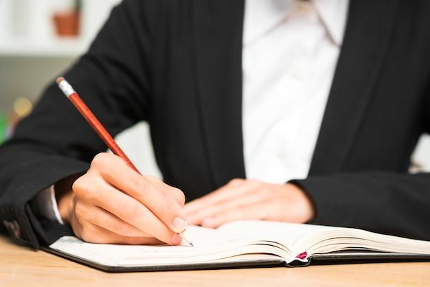 Gros plan, jeune, femme affaires, écrire, crayon rouge, journal
