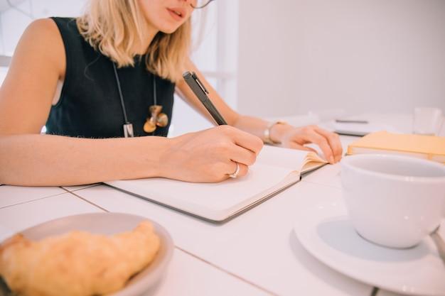 Gros plan, de, jeune femme affaires, écriture, dans journal, à, stylo, sur, table