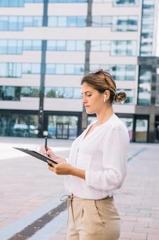 Gros plan, jeune, femme affaires, écriture, stylo, document