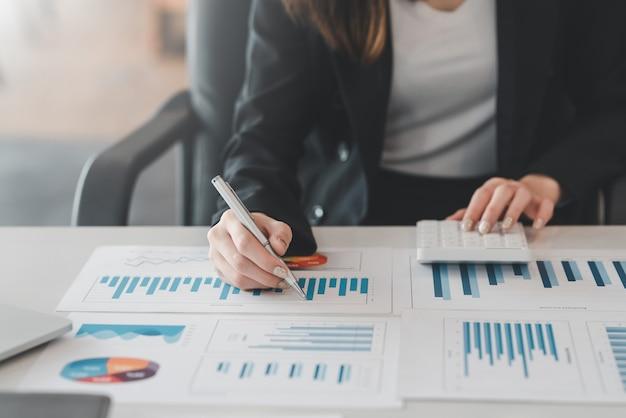 Gros plan sur une jeune femme d'affaires faisant des calculs comptables à l'aide de graphiques et de calculatrices au bureau.