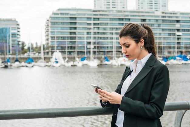 Gros plan d'une jeune femme d'affaires, messagerie texte sur téléphone portable à l'extérieur