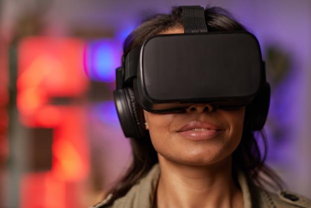 Gros plan d'une jeune femme africaine portant des lunettes pendant le jeu de réalité virtuelle