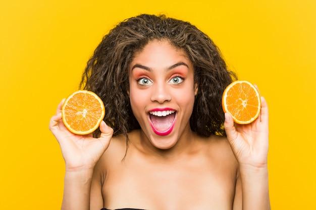 Gros plan d'une jeune femme afro-américaine belle et maquillage tenant un pamplemousse