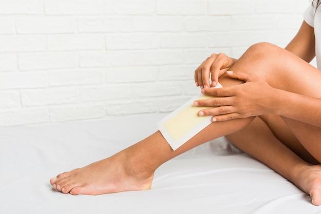 Gros plan d'une jeune femme afro-américaine cirer ses jambes