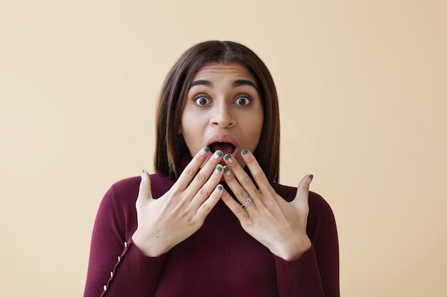 Gros plan d'une jeune femme afro-américaine étonnée drôle portant un vernis à ongles lumineux exprimant des émotions surprises, couvrant la bouche grande ouverte avec les mains. étonnement, choc et excitation