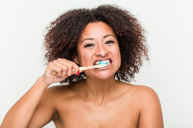 Gros plan d'une jeune femme afro-américaine se brosser les dents avec une brosse à dents