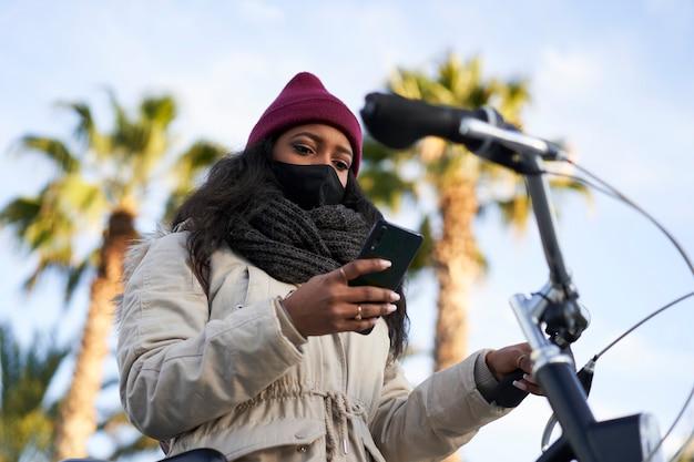 Gros plan d'une jeune femme afro-américaine sur son vélo, portant des vêtements d'hiver, à l'aide de son téléphone intelligent.
