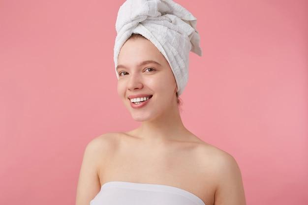Gros plan d'une jeune femme agréable positive après spa avec une serviette sur la tête, sourit largement, a l'air heureux et joyeux, se dresse.