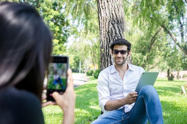 Gros plan, jeune femme à l'aide de smartphone pour prendre une photo d'un bel homme d'affaires travaillant avec une tablette dans un parc public