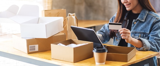 Gros plan d'une jeune femme asiatique à l'aide de tablet pc et carte de crédit pour les achats en ligne avec colis postal et sacs à provisions sur la table
