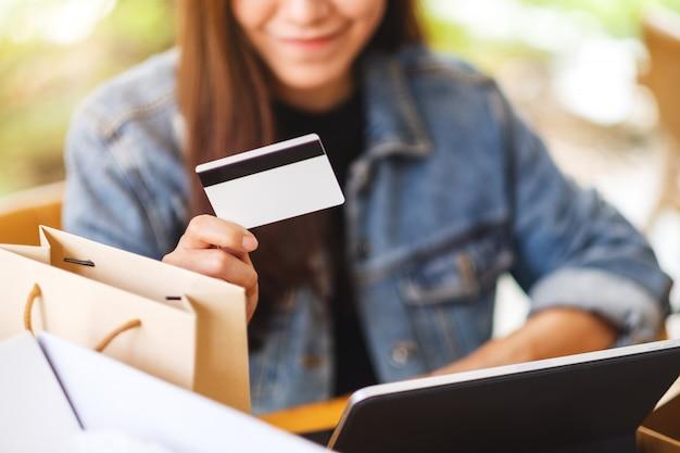 Gros Plan D'une Jeune Femme Asiatique à L'aide De Tablet Pc Et Carte De Crédit Pour Les Achats En Ligne Avec Colis Postal Et Sacs à Provisions Sur La Table Photo Premium