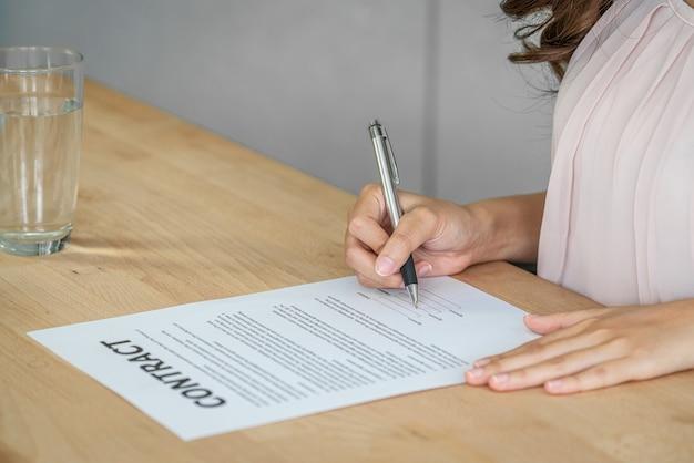 Gros plan jeune femme asiatique diplômée signant le contrat après l'entretien d'embauche