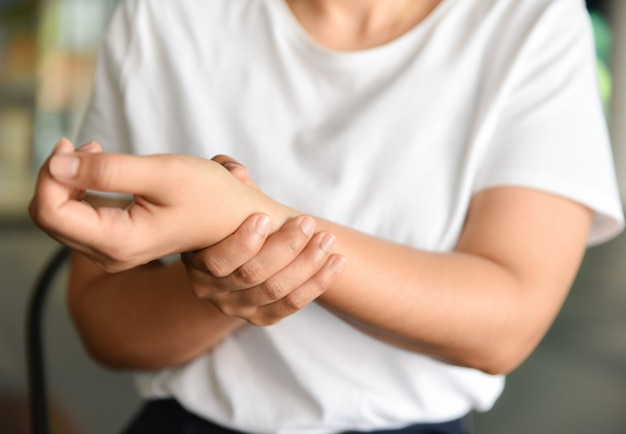Gros plan d'une jeune femme assise sur une chaise tient son poignet. blessure à la main et sensation de douleur.