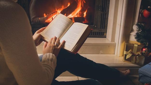 Gros plan d'une jeune femme assise près de la cheminée et lisant un livre à noël