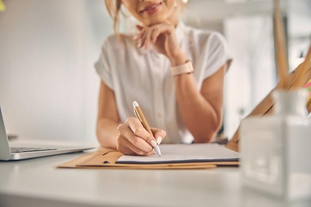 Gros plan sur une jeune femme assise à la table et faisant de la paperasse