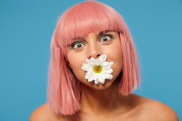 Gros plan d'une jeune femme aux cheveux assez rose avec une coupe courte autour de ses yeux verts tout en regardant la caméra, debout sur fond bleu avec une fleur blanche dans sa bouche