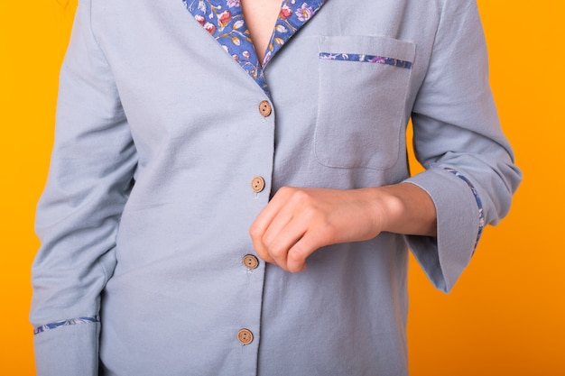 Gros plan de la jeune femme aux cheveux bouclés en bleu home wear. isolé sur mur jaune.