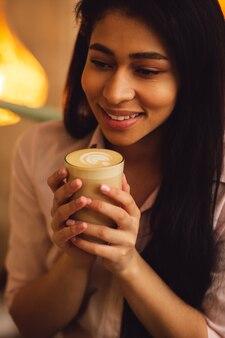 Gros plan d'une jeune femme aux cheveux noirs heureuse se sentant bien et souriante tout en tenant un verre de latte