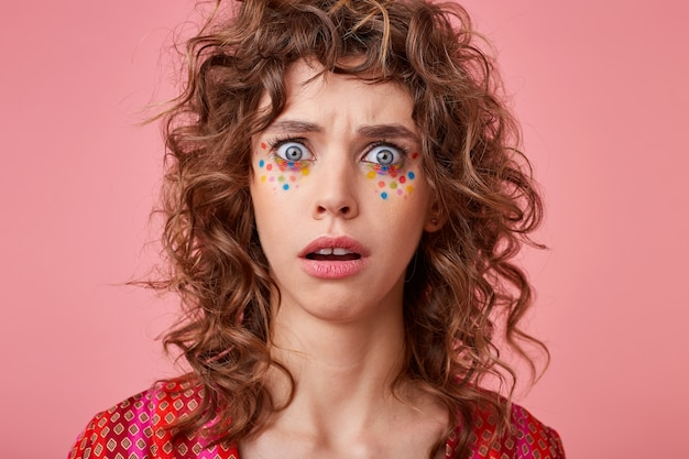 Gros plan d'une jeune femme aux yeux grands ouverts, à la recherche, isolée, portant des vêtements rayés roses et orange