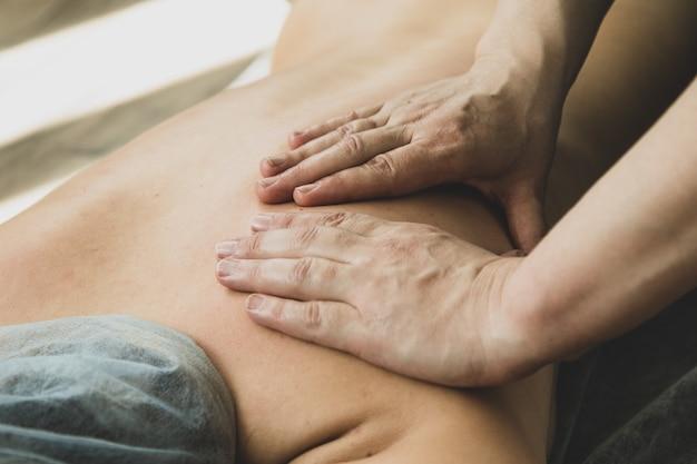 Gros plan, jeune femme, avoir, massage shiatsu, par, professionnel, sur, plancher bois, chez soi
