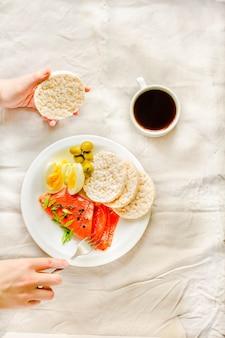 Gros plan de jeune femme ayant une pause déjeuner. repas riche en protéines et faible en glucides. concept de régime paléo. vue de dessus.