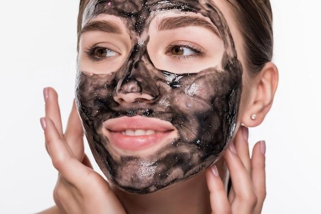 Gros plan d'une jeune femme de beauté à l'aide d'un masque noir isolé