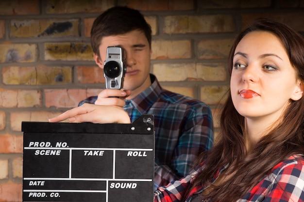 Gros plan jeune femme blanche avec clapper board, regardant le côté gauche, devant le photographe masculin prenant une photo.