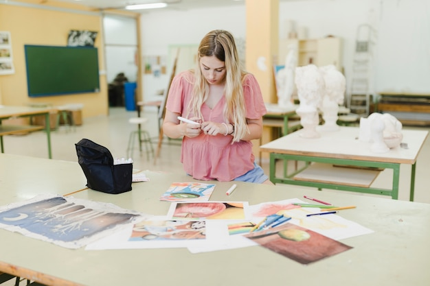 Gros plan d'une jeune femme blonde faisant des peintures sur papier sur table