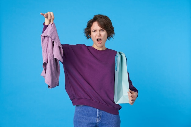 Gros plan de jeune femme bouclée aux cheveux noirs agacé en gardant sa main levée