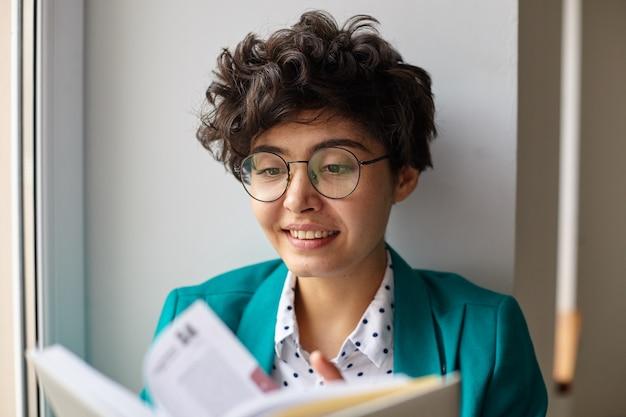 Gros plan d'une jeune femme brune frisée aux cheveux courts aux yeux bruns, retournant le livre avec enthousiasme et souriant agréablement tout en posant sur un intérieur blanc sur une journée ensoleillée