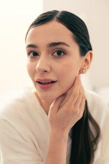 Gros plan d'une jeune femme calme à l'air détendue et souriante en se tenant debout avec un peignoir et en lui touchant la joue