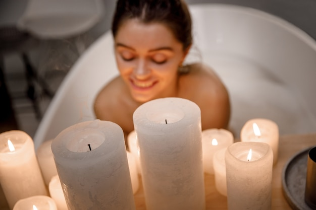 Gros plan sur une jeune femme calme se relaxant dans la belle baignoire vintage pleine de mousse dans la salle de bain rétro, décorée de bougies. traitement sain et plaisir.