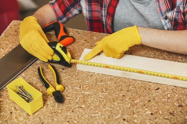 Gros plan sur une jeune femme caucasienne aux cheveux bruns en chemise à carreaux, t-shirt gris, gants jaunes travaillant dans un atelier de menuiserie sur une table en bois avec différents outils, mesurant la longueur de la barre par un ruban à mesurer