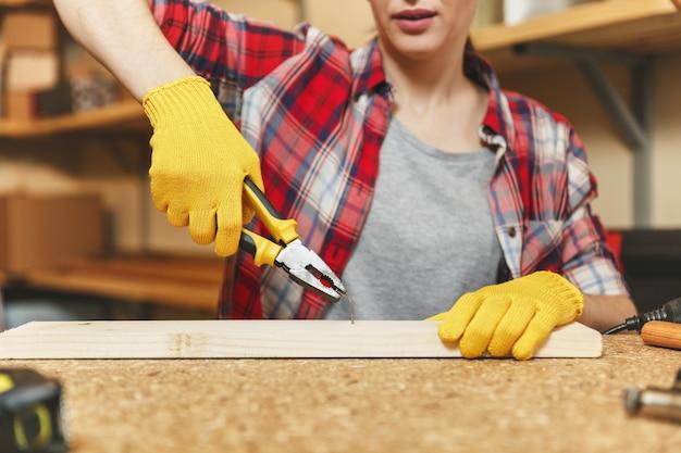 Gros plan sur une jeune femme en chemise à carreaux, un t-shirt gris, des gants jaunes travaillant dans un atelier de menuiserie sur une table en bois avec différents outils, enlevant le clou avec une pince après avoir enfoncé le panneau.