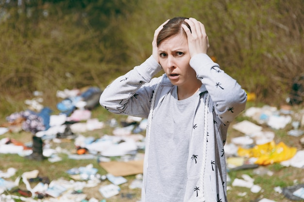Gros plan jeune femme choquée dans des vêtements décontractés nettoyant accroché à la tête près d'un tas d'ordures dans un parc jonché