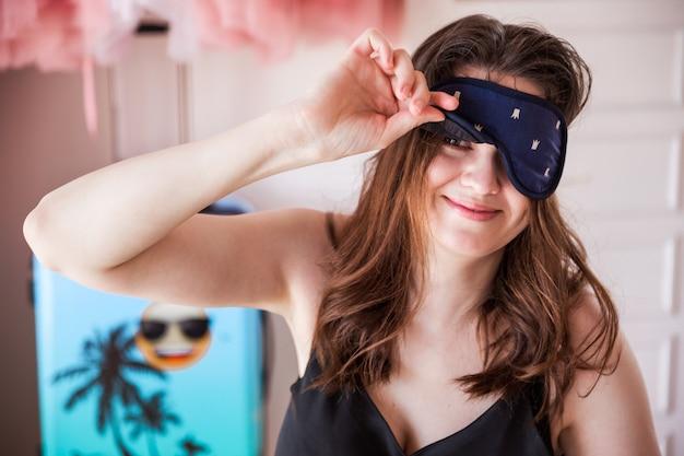 Gros plan d'une jeune femme dans la chambre le matin avec un masque de sommeil, regardant la caméra avec un sourire positif, profitant du temps libre dans la chambre.