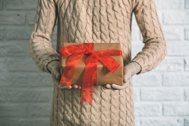 Gros plan sur la jeune femme dans des gants en caoutchouc tenant un cadeau