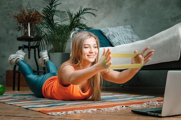 Gros plan d'une jeune femme dans un uniforme de sport se repose, fait de l'exercice le matin, s'étire avec des élastiques de remise en forme sport