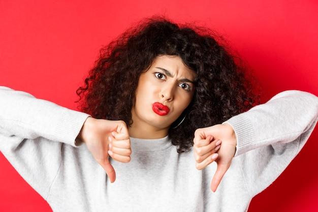 Gros plan d'une jeune femme déçue avec une coiffure frisée montrant les pouces vers le bas et les sourcils froncés condamne donc...
