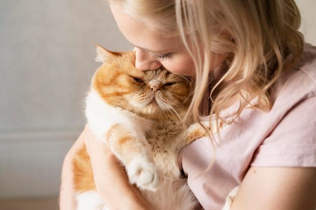 Gros plan jeune femme embrassant un chat mignon