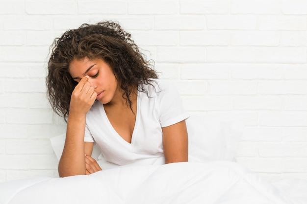 Gros plan d'une jeune femme fatiguée afro-américaine assise sur le lit