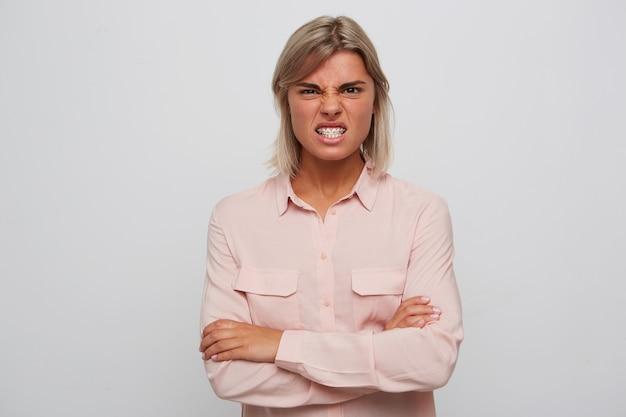 Gros plan d'une jeune femme folle folle aux cheveux blonds et accolades sur les dents porte chemise rose