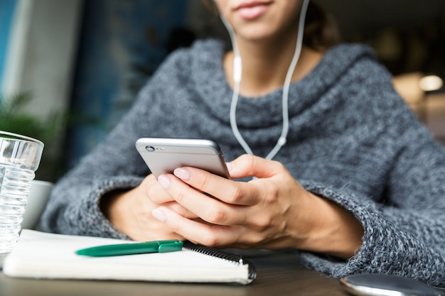 Gros plan d'une jeune femme habillée en pull assis dans une chaise à la table du café, écouter de la musique avec des écouteurs, à l'aide de téléphone mobile
